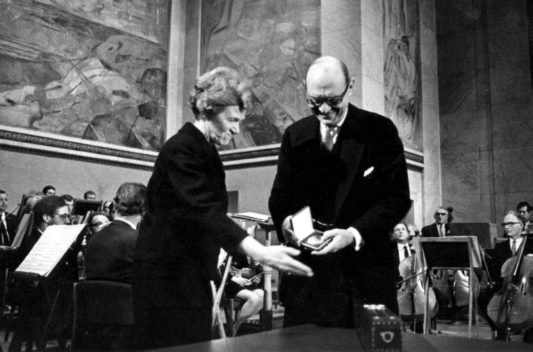 1969-10-10, ILO Director-General David A. Morse receives the 1969 Nobel Peace Prize on behalf of the ILO from Aase Lionaes, Chairman of the Nobel Committee of the Norwegian Parliament, in the Aula of the University of Oslo. ILO historical archives.